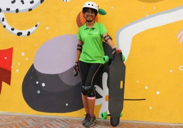 Jam with her skateboard with a yellow wall